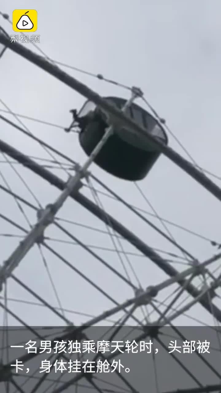 [视频]男孩乘摩天轮头被卡,身体悬挂舱外