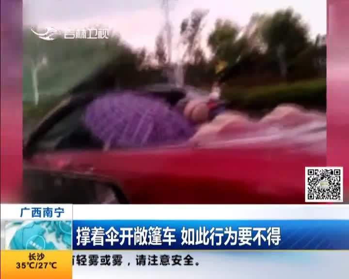 [视频]撑着伞开敞篷车 如此行为要不得